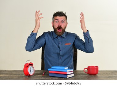Man with shocked face sits at wooden table. Cup and retro clock with red and blue books on vintage table. Deadline and work concept. Manager with beard and glasses on head isolated on white background