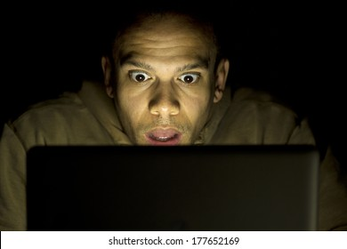 A man with a shocked look on his face at night on his laptop.