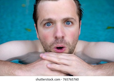 Man is shocked with news. He is closing his mouth in surprise. He is swimming in pool during vacation