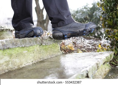 A Man with Shoe snow spikes in winter on icy stairs