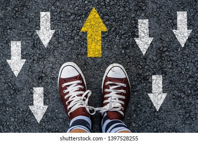 man shoes asphalt and opposing direction arrows on asphalt ground, personal perspective footsie concept for finding your own way