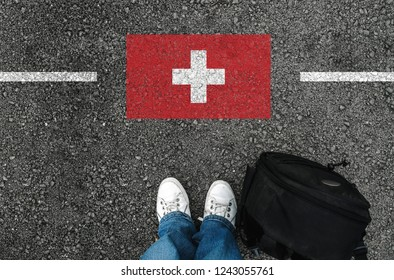 a man with a shoes and backpack is standing on asphalt next to flag of Switzerland and border