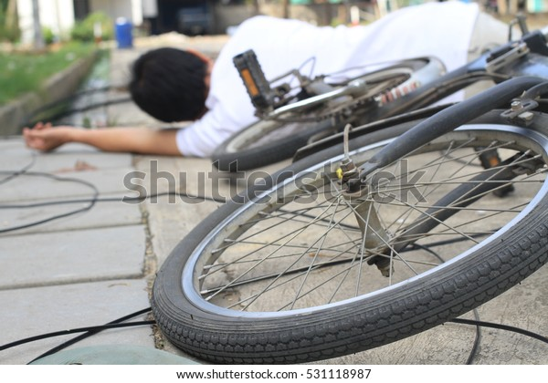 man , Shoes and bicycle  lay down near Power light pole crash across road with accident