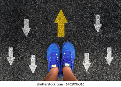 man shoes on asphalt and opposing direction arrows on asphalt ground, personal perspective footsie concept for finding your own way