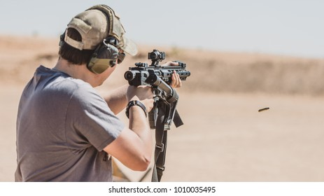 Man shooting black rifle on desert range folding stock
