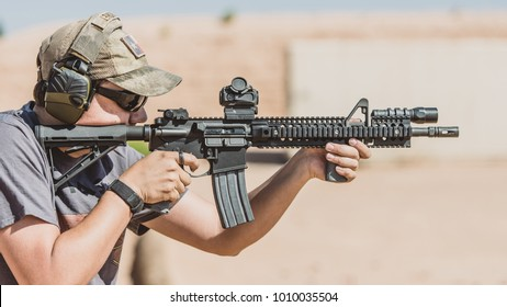 Man shooting black rifle on desert range wide shot