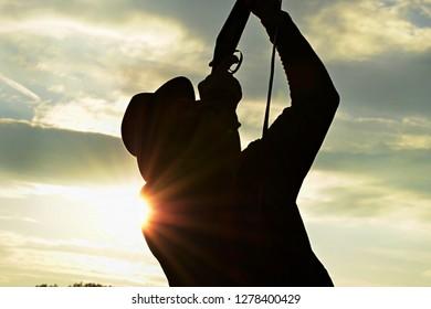 man shooting ducks with a shotgun, silhouette against the sundown