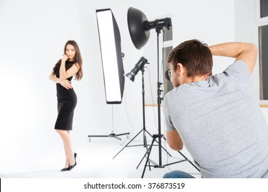 Man shooting female model in studio with softboxes