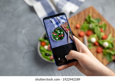 Man shooting fresh vegetable salad with mozzarella and spinach on cell phone camera. Cooking, blogging and healthy eating concept.