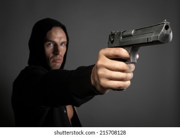 man shooting gun isolated on gray background. focus on gun