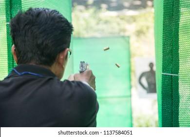 man shooting gun pistol automatic range fire to target handgun speed shooting competition