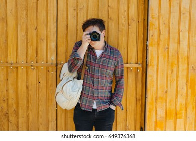 Man shooting photos on the wooden background. Boy with camera and backpack. Cameraman. Operator shooting video.