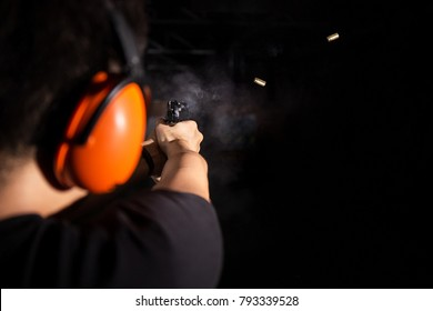 man shooting pistol gun, extreme sport, fire bullet, and wear orange ear cover, safety glasses, equipment in professional and safety shooting range with smoke and bullet shell on black background