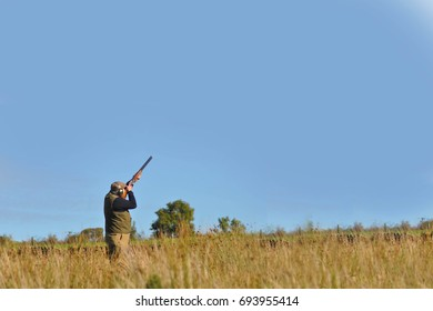 Man shooting with shotgun with a blue sky background for copy text Ireland 2017