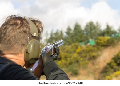 man shooting shotguns at clay pigeon outdoors