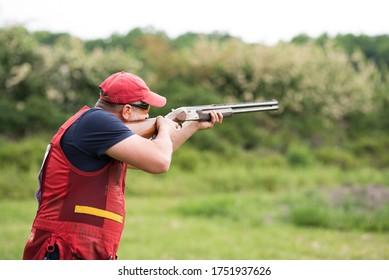Man shooting skeet with a shotgun.