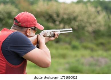 Man shooting skeet with a shotgun. Skeet shooting, trap shooting.
