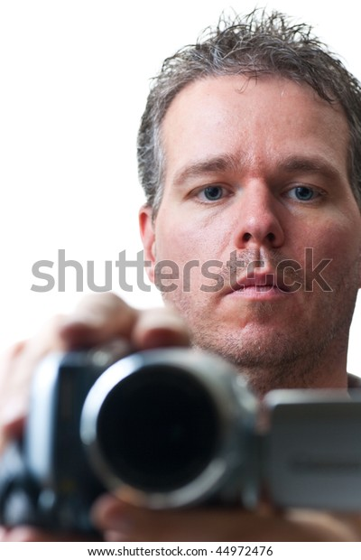 A man shooting with a video camera, focus on the man's face, isolated on white.