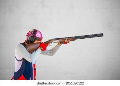A man shoots a double-barreled shotgun at a sports shooting range, shooting at moving targets