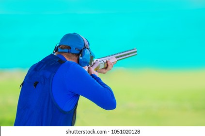 A man shoots a double-barreled shotgun at a sports shooting range, shooting at moving targets