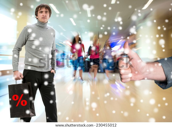Man with shopping bag, another man gesturing thumb up at shopping mall. Christmas and holidays concept