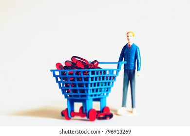 Man with shopping cart full of pills. Pharmacy shopping or purchasing medicine or painkillers. Stocking up and saving money on healthcare prescriptions. Miniature person buying drugs. Pharmaceuticals.