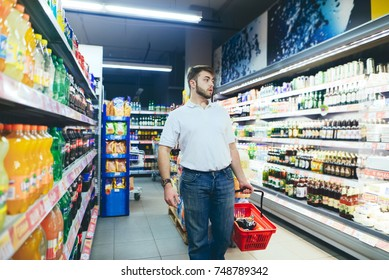A man with a shopping cart in his hands goes to the supermarket and looks at the sides. The buyer chooses the products in the supermarket
