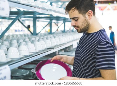 Man shopping for ceramics, plates, and homeware in a factory outlet store