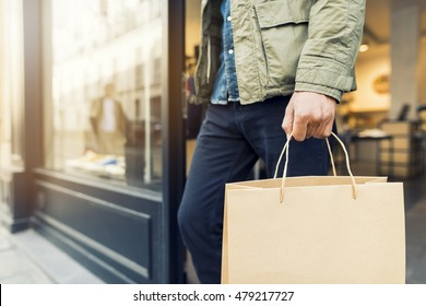 Man shopping in clothing store carry a paper bag
