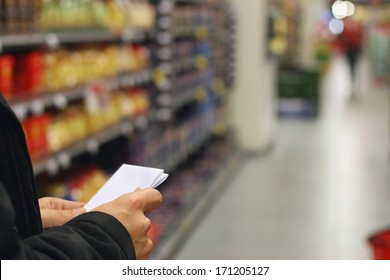 A man with shopping list, grocery store shelves and products in background