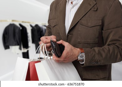 Man shopping. Male holding shopping bags and wallet.