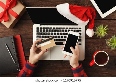 Man shopping online with credit card and smartphone with blank screen. Top view on human hands, keyboard, coffee, Santa hat, Christmas gift on wooden table background. New Year, holiday concept