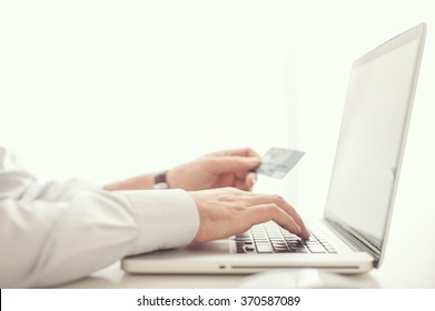 Man shopping online with his credit card from his laptop computer