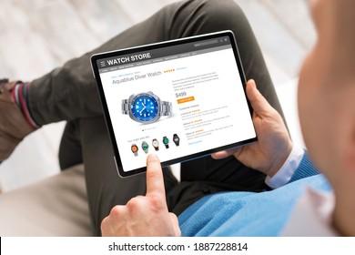 Ein Mann, der online auf einem Tablet-Computer einkauft, für eine neue Uhr
