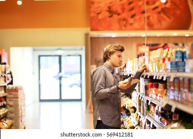 Man shopping in supermarket reading product information.Using smarthone