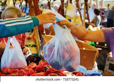 Man shopping vegetables at the market. Farmer vendor hands over plastic bag filled with fresh vegetables to a buyer in CLUJ-NAPOCA, ROMANIA - SEPTEMBER 16, 2017