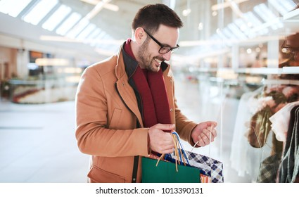 Man in shopping. Young man in shopping mall looking for presents. Consumerism, shopping, lifestyle concept