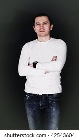 Man with short hair in casual wear posing in the studio. Dark background.