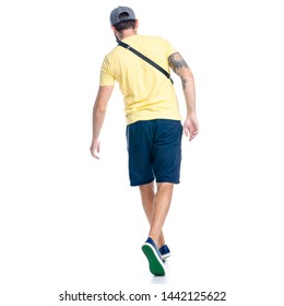 Man in shorts and cap walking goes running happiness smiling on white background isolation, back view