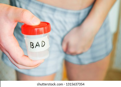 A man in shorts in his hands analysis of sperm labeled bad. Close-up of a hand with a jar of analysis. Bad analysis, unsuccessful, health problems