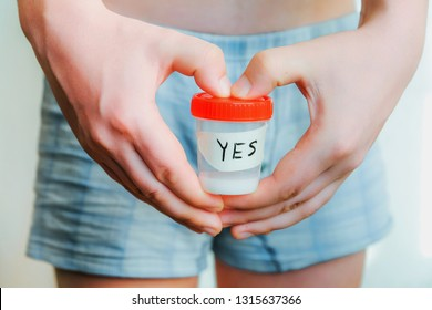A man in shorts holds a sperm analysis with the words yes. Hands in the shape of a heart. Close-up of hands and analysis jars. Good analysis