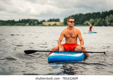 a man in shorts sitting relaxed on a supsurf