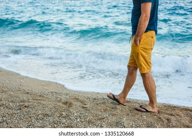 Man in shorts walking on the beach