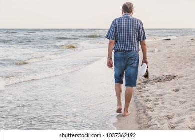 Man in shorts walking on sea beach summer evening