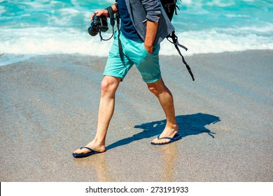 Man in shorts walking with photo camera on the beach