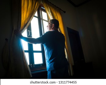 Man shot against the light of a window