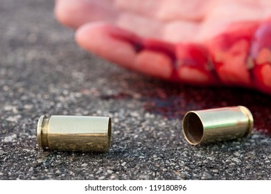A man shot in the streets with the bullet casing laying next to a bloody hand.