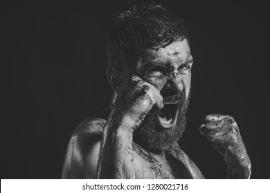 Man shout in fight position with blood paint on face, fists. Bearded hipster with tattoo on chest on black background. Power, might, magic. Sport, boxing, fighting. Halloween, holidays celebration.