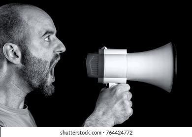man shouting into megaphone black background