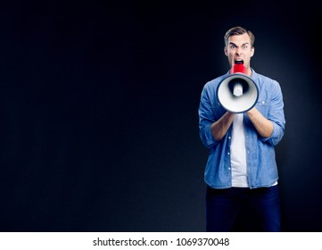 Man shouting through megaphone, with empty copyspace area for slogan, advertising or text message, over black background. Caucasian male model in blue smart casual clothing making announcement.